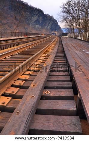 Train Tracks lead to Tunnel - stock photo