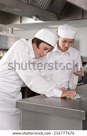 Trainee chefs cleaning work surface in commercial kitchen - stock photo