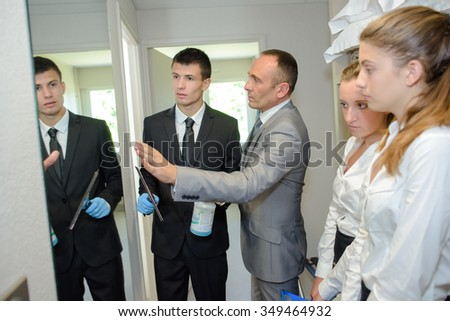 Trainee cleaning a mirror under supervision - stock photo