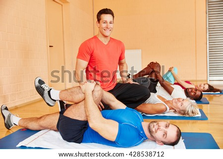Trainer and people during rehab class following instructions from coach - stock photo
