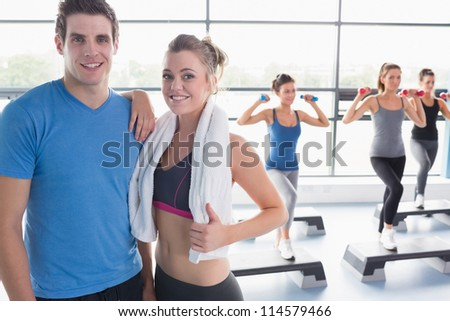 Trainer and woman smiling together while aerobics class taking place in gym - stock photo