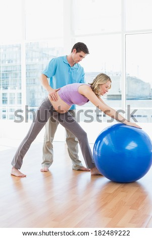 Trainer exercising with pregnant client and exercise ball in a studio