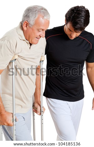 Trainer helping senior man with crutches to walk over white background - stock photo