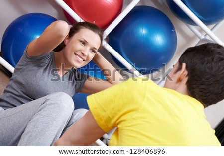 Trainer holding young woman doing sport fitness press in gym - stock photo