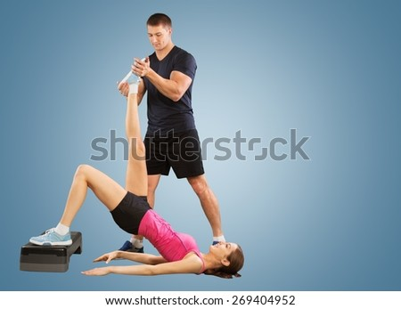 Trainer. Personal trainer man coach and woman exercising abdominals push ups on bosu silhouette  studio isolated on white background - stock photo