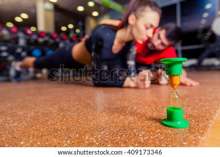 Trainer supervising a muscular woman doing plank exercises, exercise strap. - stock photo