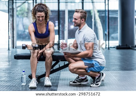 Trainer supervising a muscular woman lifting a dumbbell - stock photo