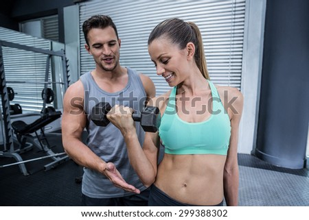 Trainer supervising a muscular woman lifting dumbbells - stock photo