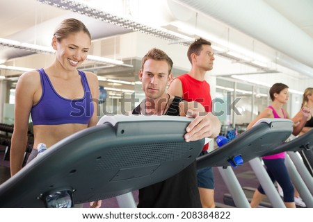 Trainer talking to his client on the treadmill at the gym - stock photo