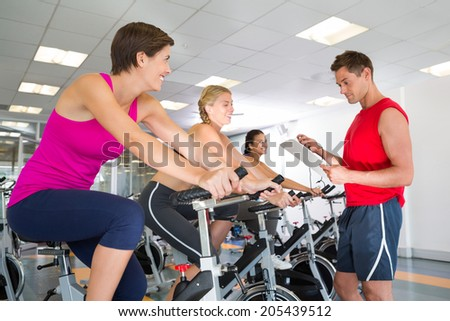 Trainer talking with his spin class at the gym - stock photo