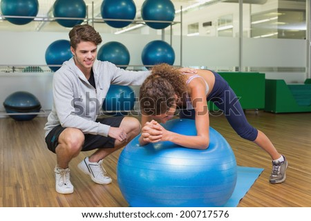 Trainer watching his client using exercise ball at the gym - stock photo