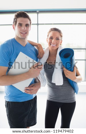 Trainer with a happy client in gym - stock photo