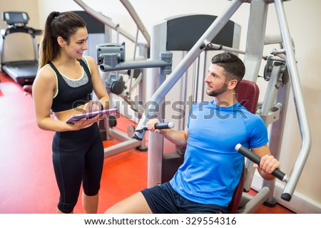 Trainer working with athlete at weights machine at the gym - stock photo