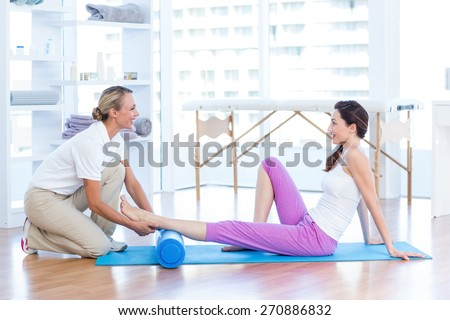 Trainer working with woman on exercise mat in medical office - stock photo