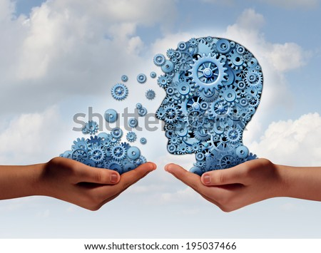 Training and development business education concept with a hand holding a group of gears transferring the wheels to a human head made of cogs as a symbol of acquiring the tools for career learning. - stock photo