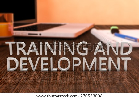 Training and Development - letters on wooden desk with laptop computer and a notebook. 3d render illustration. - stock photo