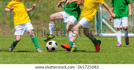 Training and football match between youth soccer teams. Young boys playing soccer game. Hard competition between players running and kicking soccer ball. Final game of football tournament for kids. - stock photo