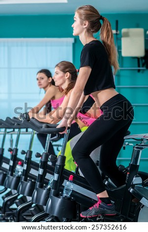 Training on a bicycles. Athletic girl pedaling on the simulator until her four girlfriends athletes pedaling on a stationary bike at the gym. - stock photo