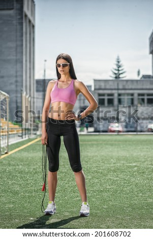 Training on the force. Young beautiful woman in sportswear standing on the field with a rope in his hand and looking straight into the camera postvio hand on his torso - stock photo