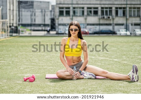 Training with dumbbells. Girl with dumbbells sitting on field holding a bottle of water and drinking water - stock photo