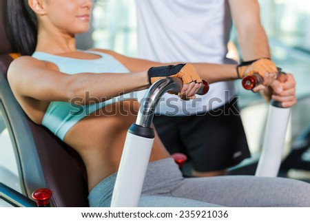 Training with instructor. Close-up of beautiful young woman working out in gym while instructor supporting her - stock photo