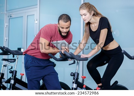 Trainings with a coach. Athletic girl pedaling on a stationary bike in the gym while the coach on the tablet shows how to pedal - stock photo