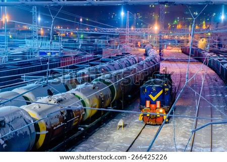 Trains of oil tanks and wagons on the cargo railway station at winter night - stock photo