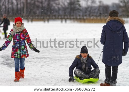 TRAKAI, LITHUANIA - JANUARY 7, 2016: Children having a slide on the ice in winter Trakai. Having a slide on the ice involves any activity which consists of traveling on surfaces or on ice.