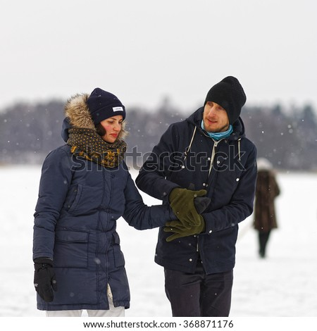 TRAKAI, LITHUANIA - JANUARY 7, 2016: Young couple in winter rink in Trakai at snow fall. Selective focus.