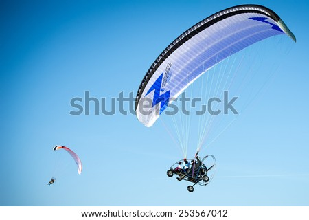 TRAKAI, VILNIUS-FEB 14: Powered Paraglider (paramotor) in winter over ice covered lake Galve on Feb. 14, 2015 in Trakai, Lithuania. Trakai is one of the most popular tourist destinations in Lithuania. - stock photo