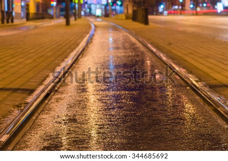 Tram rail track wet and shiny by night lights, blurred city background - stock photo