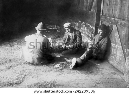 Tramps traveling in a freight car pass the time playing cards. Migrant laborers hopped box cars to seek work. Ca. 1910. - stock photo