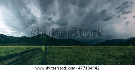 Tramps walking along the road track on background of mountains and storm, Altai, Russia