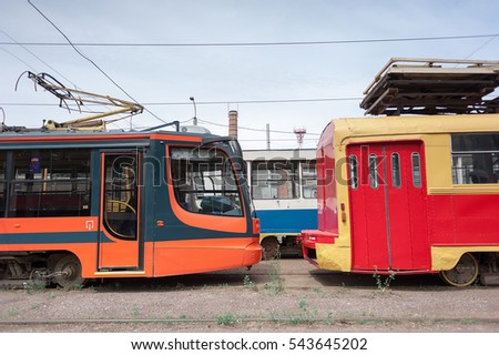 Trams new and old, are in a park, ready to travel the route. past  future