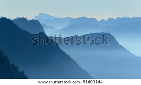 Tranquil and foggy sunrise in the mountains of the Swiss Alps.