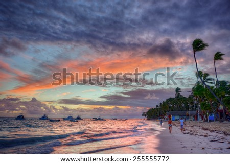 Tranquil beach at sunset with boats and meandering people - stock photo
