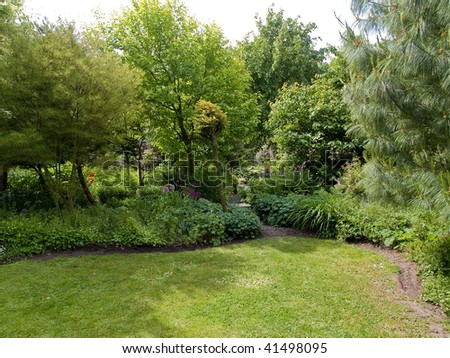 Tranquil Beautiful Garden with Lush Green Trees and Grass - stock photo