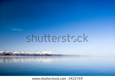 tranquil lake and snow mountains in the morning - stock photo