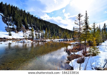 Tranquil lake scene with snow during early spring - stock photo