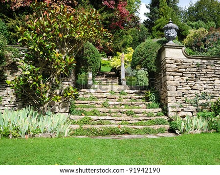 Tranquil Landscape Garden Scene of a Freshly Mown Lawn and Steps to an Upper Level - stock photo
