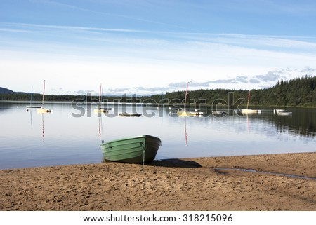 Tranquil Loch with Boats: a green boat partially hauled up onto a sandy beach, infront of a group of sailing boats floating on a very calm loch.  Loch Morlich, Cairngorm National Park Scotland - stock photo