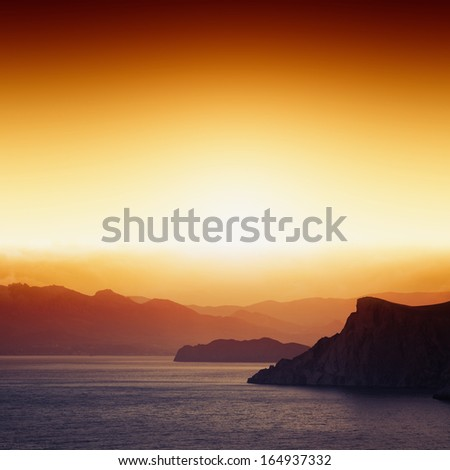 Tranquil peaceful landscape - beautiful red sunset, mountain silhouettes  - stock photo