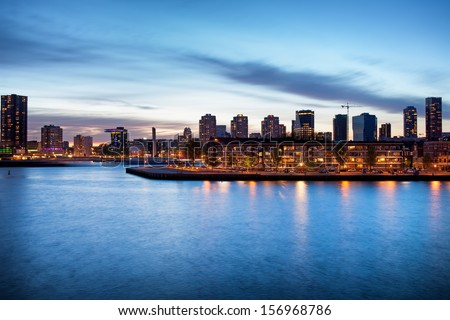 Tranquil river view of the Rotterdam city centre in Holland, Netherlands at dusk. - stock photo