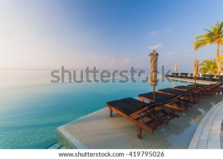 Tranquil scene of a swimming pool and beach with palm trees and white sand - stock photo