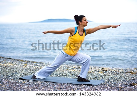Tranquil scene of a young woman doing a pilates pose on the beach - stock photo