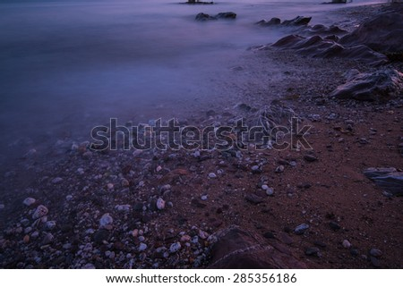 Tranquil seascape on rocky beach at twilight, with waves motion blur - stock photo