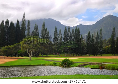 Tranquil setting of a golf course with a mountain background in Kauai, Hawaii - stock photo