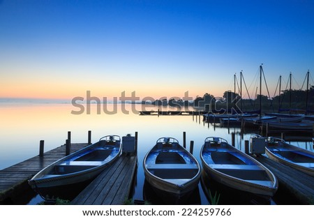 Tranquil sunrise at a small marina on a lake. - stock photo