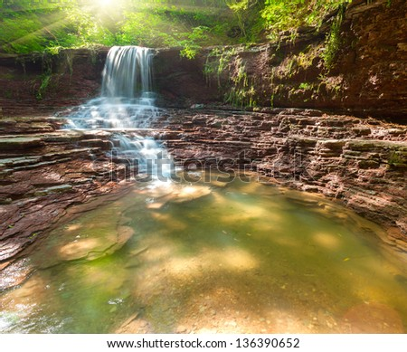 Tranquil waterfall scenery in the middle of green forest - stock photo
