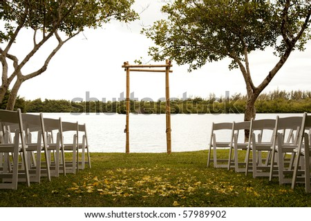 Tranquil wedding setting with trellis, water and trees - stock photo